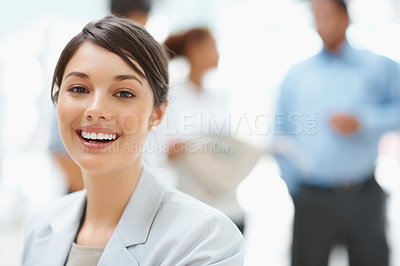 Buy stock photo Portrait of a happy business woman with colleagues discussing in background