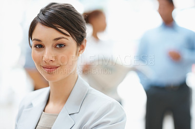 Buy stock photo Portrait of a successful business woman smiling with colleagues in the back