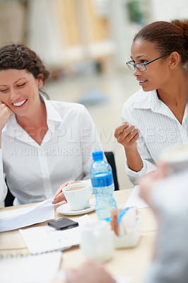 Buy stock photo Smiling women sitting together at a business meeting