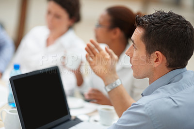 Buy stock photo Young business man with a laptop , giving his point of view during a meeting
