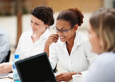 Buy stock photo Smiling African American business woman sitting with her team at a meeting