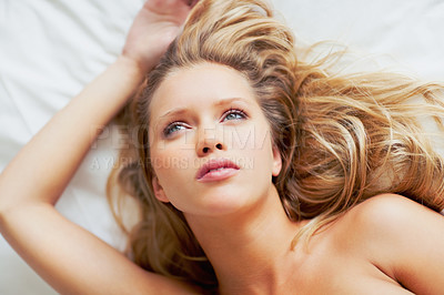 Buy stock photo Top view of a thoughtful pretty young woman lying on bed