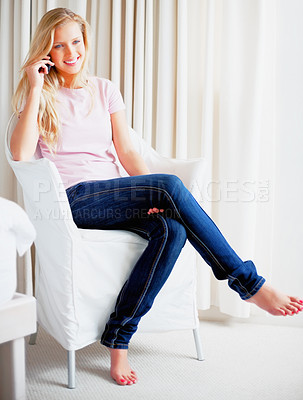 Buy stock photo Young Caucasian girl sitting on armchair and talking on a cell phone at home
