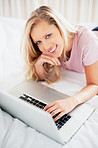 Happy young female browsing the internet on bed
