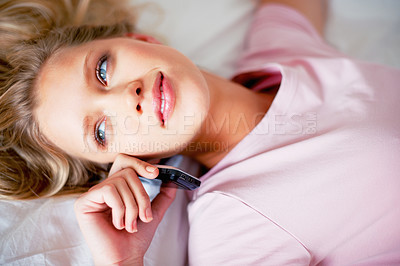 Buy stock photo Closeup of a beautiful smiling woman lying on bed while talking on cellphone