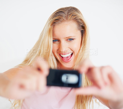 Buy stock photo Smiling pretty woman taking a picture of herself through a cell phone