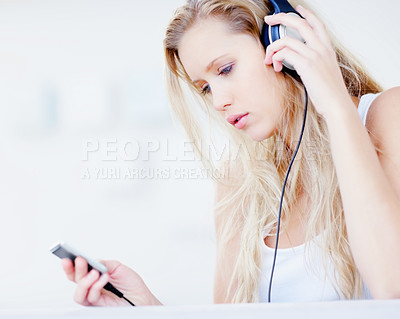 Buy stock photo Young woman listening to songs from the music player over the headphones