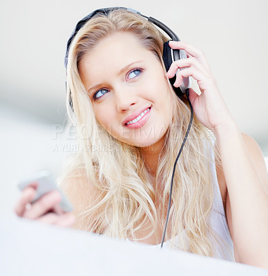 Buy stock photo Portrait of a smiling pretty woman listening to music over headphones