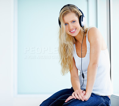 Buy stock photo Pretty young female listening to music over headphones with copyspace