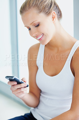 Buy stock photo Smiling cute female reading a text messaging on the cellphone