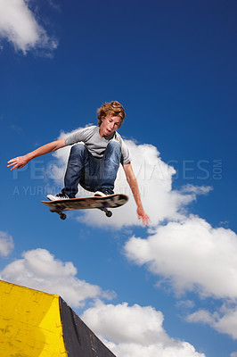 Buy stock photo A teenager jumps a ramp on his skateboard - Copyspace