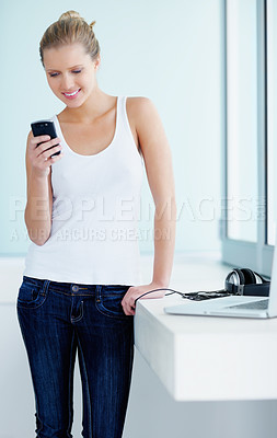Buy stock photo Portrait of a smiling young female reading a text message by the window sill