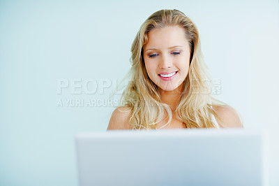 Buy stock photo Portrait of a smiling young blond female using a laptop at home