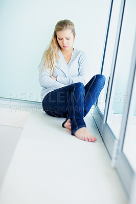 Buy stock photo Portrait of a sad young thoughtful woman by the window