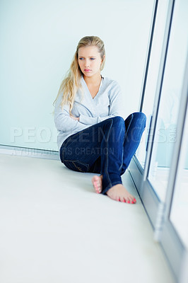 Buy stock photo Depressed young female sitting against a wall by a window