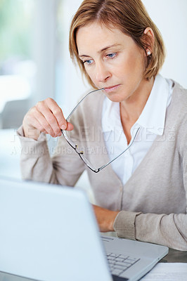 Buy stock photo Portrait of middle aged woman holding glasses in mouth while working at her desk