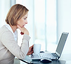Surprised mature businesswoman looking at laptop holding cup of