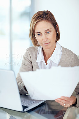 Buy stock photo Portrait of confident mature businesswoman checking the documents at office