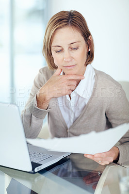 Buy stock photo Portrait of mature businesswoman reading the documents in office