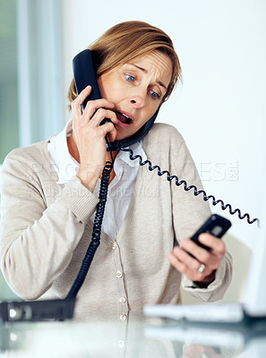Buy stock photo Portrait of surprised mature businesswoman multitasking by handling telephone calls