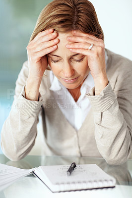 Buy stock photo Portrait of tensed mature businesswoman holding her head while at work