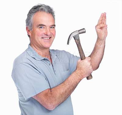 Buy stock photo Portrait of a mature man hammering a nail into the wall against white background