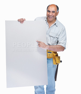 Buy stock photo Portrait of a happy mature handyman pointing at a blank billboard isolated on white