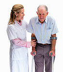 Nurse helping a senior man on crutches against white background