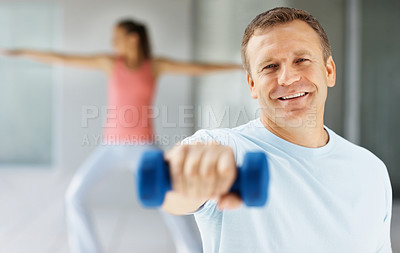 Buy stock photo Portrait of a smiling middle aged man working out at the gym , female at the back