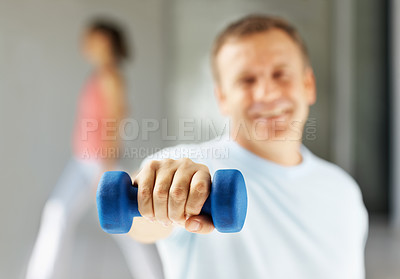 Buy stock photo Man using a dumbbell to work out at the gym with the focus on his hand