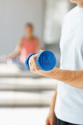 Buy stock photo Mid section closeup of a man using a dumbbell to work out at the gym