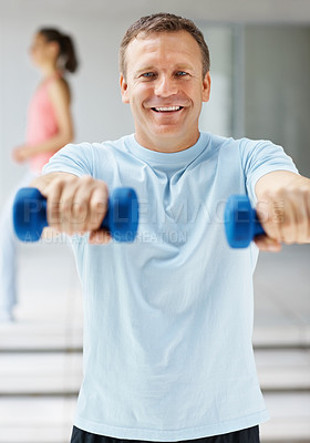 Buy stock photo Portrait of a happy middle aged guy using dumbbells while at the gym