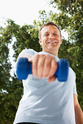 Buy stock photo Portrait of a happy middle aged guy using dumbbells outdoors
