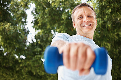 Buy stock photo Portrait of a smiling man working out with a dumbbell while outdoors