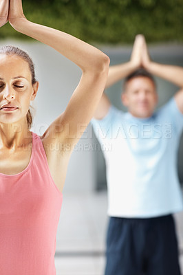 Buy stock photo Portrait of a spiritual female practicing yoga with a man at the back