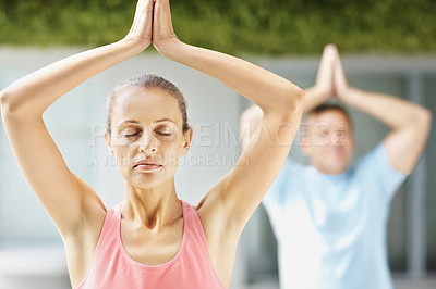 Buy stock photo Portrait of a fit female practicing yoga with hands joined above head and a man at the gym
