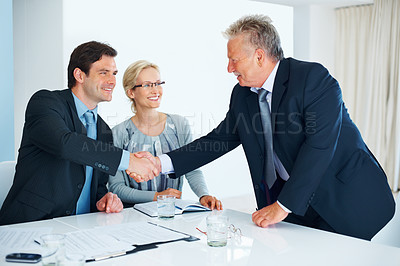 Buy stock photo Portrait of senior business man giving handshake to male executive with female colleague in office