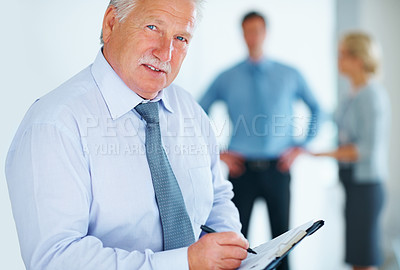 Buy stock photo Portrait of senior business man taking notes with colleagues in background