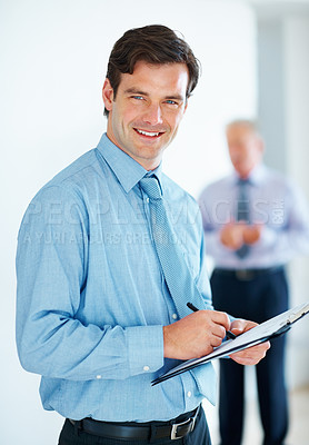 Buy stock photo Portrait of young business man taking notes with colleagues in background