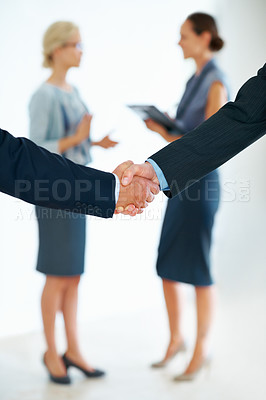 Buy stock photo Closeup of business men shaking hands with female executives in background
