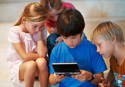Buy stock photo Portrait of cute boy playing video game with friends looking on