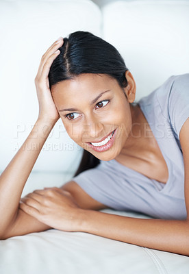 Buy stock photo Pretty mixed race woman relaxing on couch, looking away