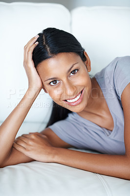 Buy stock photo Portrait of beautiful mixed race woman smiling while lying on couch