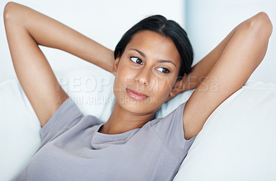 Buy stock photo Closeup of attractive mixed race woman relaxing on couch while looking away
