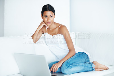 Buy stock photo Attractive mixed race woman lounging on her couch with her laptop, looking away thoughtfully - copyspace