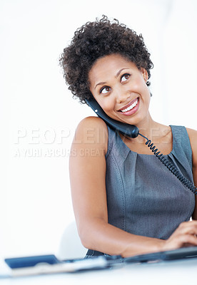 Buy stock photo Attractive female executive talking on phone while using computer on white background