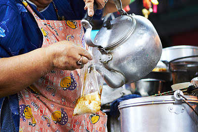 Buy stock photo Woman wearing an apron pours content of kettle over food in a plastic bag
