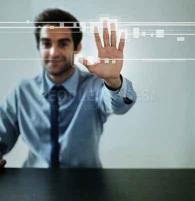 Buy stock photo A handsome man connecting to a user interface with his hand