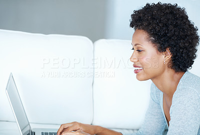 Buy stock photo Smiling African American woman surfing internet while lying on couch