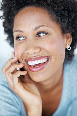 Buy stock photo Closeup of charming young woman smiling while talking on mobile phone